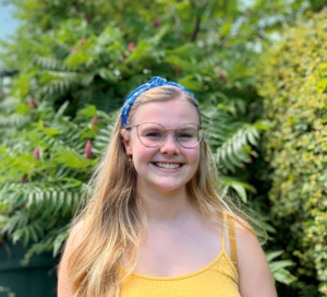 Catrin has long blonde hair and a yellow top on. She is smiling in front of a leafy background. Read her student profile for more information.